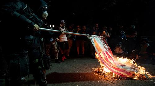المتظاهرون اليساريون يحرقون الكتاب المقدس والعلم الأمريكي في مظاهرة بورتلاند