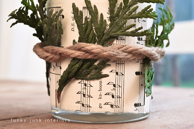 candle wrapped with twine, sheet music and greens