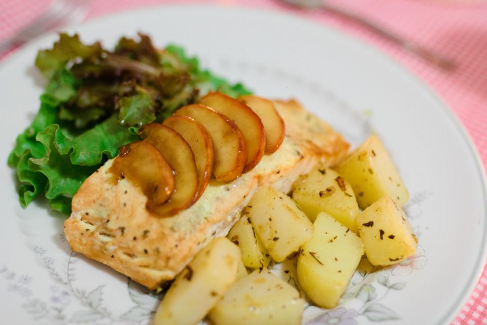 Salmão grelhado acompanhado de batatas e molho de iogurte e ervas finas