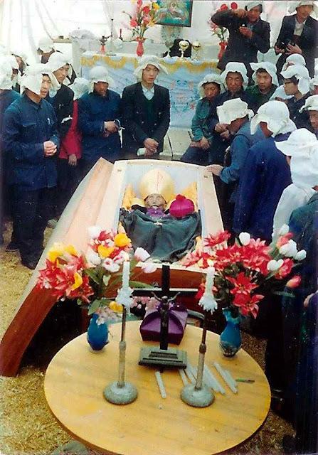 Funeral de Mons. Xue-Yan Fan, antigo bispo de Baoding. Seu corpo com muitos ossos quebrados, foi despejado, envolto em plástico