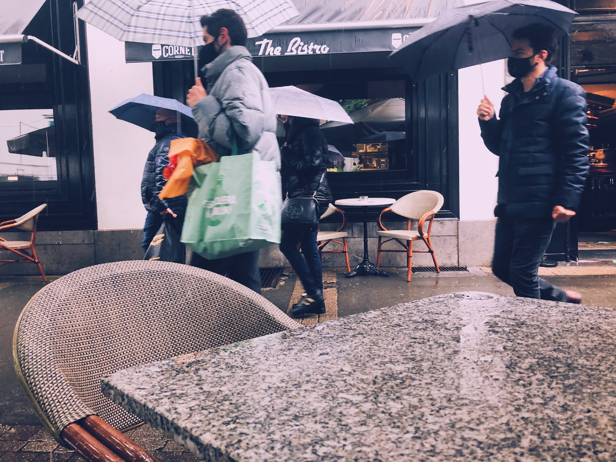 Foto van voorbijgangers met een paraplu in handen genomen vanop een terras.