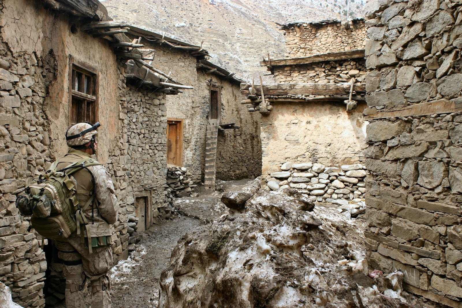 a soldier walks through an alley of a battered afghanistan town to illustrate a blog post about the documentary the battle of marjah
