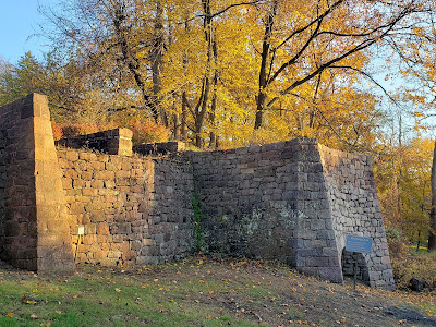 Golden fall foliage and late afternoon sun with stone walls of iron ore roasting oven