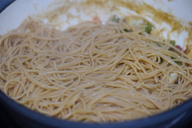 The noodles being added to the pan.
