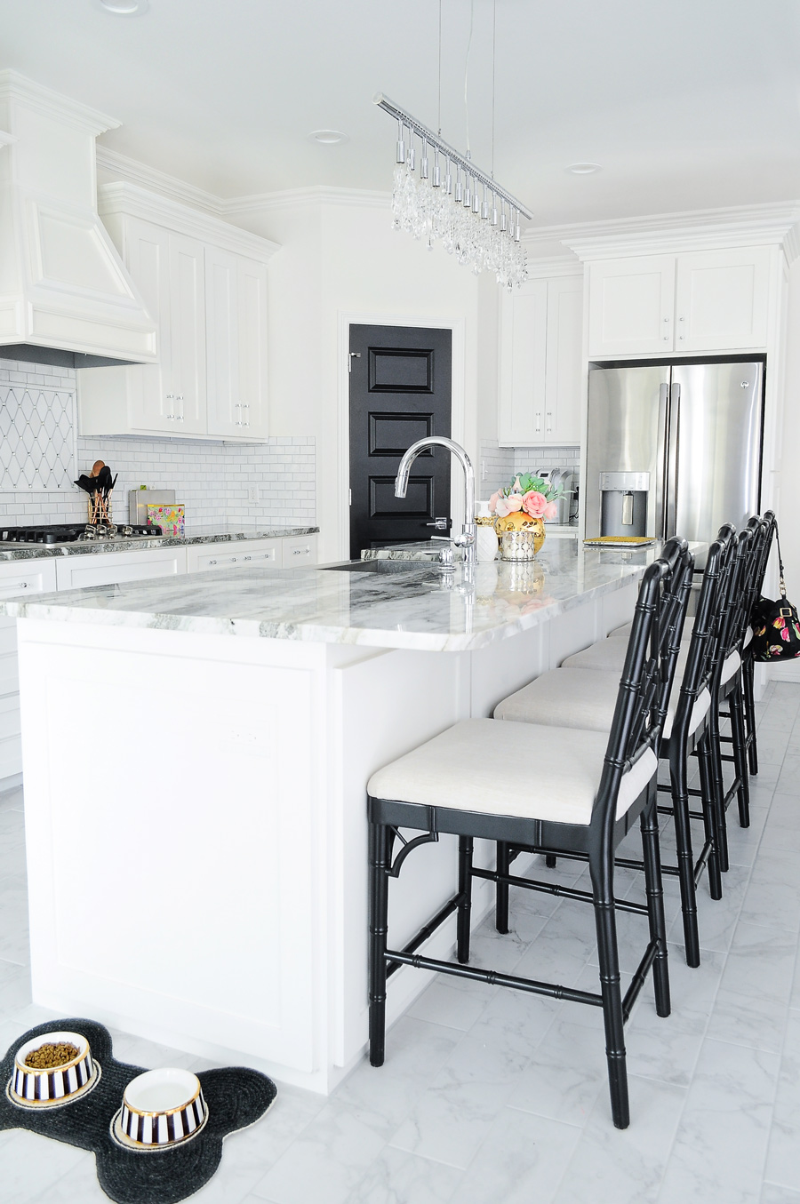 Bright white kitchen with fantasy brown granite, marble backsplash, thassos mirrored backsplash and lucite cabinet and drawer pulls. The Dayna counter stools from Ballard Design and crystal linear chandelier are gorgeous!