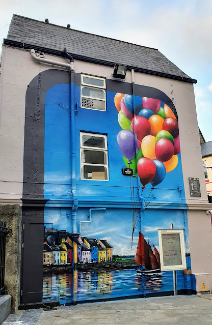 Side of building size painting of the Long Walk and River Corrib with a Galway Hooker, and a large bunch of multi-coloured balloons
