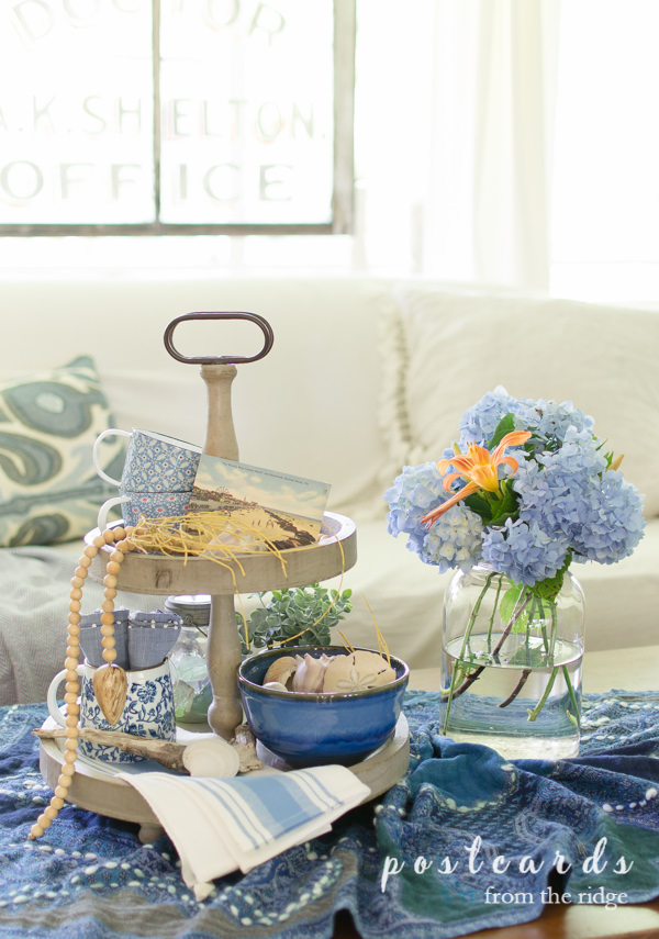 blue hydrangeas in a mason jar with blue and white decorated tiered tray
