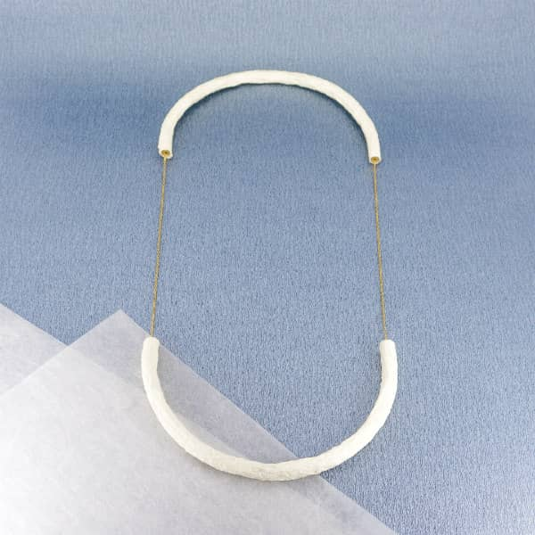necklace of two semi-circular white paper shapes attached with brass chains