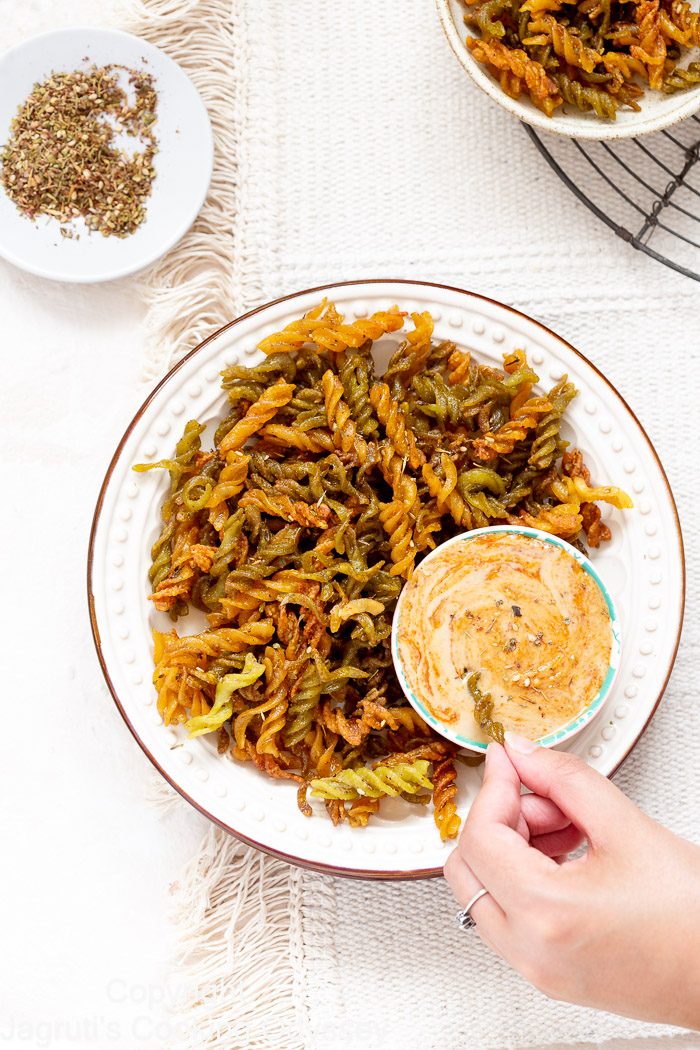 Air fryer lentil pasta chips served in a plate with tahini dip
