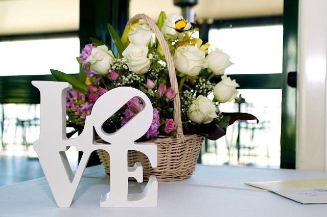 Imagem mostra cesta de flores e escultura com a palavra Love sobre a mesa
