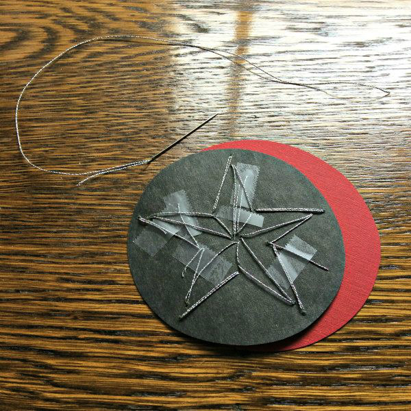 reverse side of paper stitched star ornament with silver thread and needle