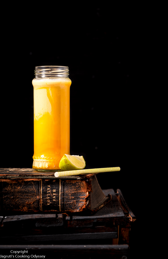 This yellow Indian style mango yogurt drink is in bottled jar and served  with yellow paper straw.