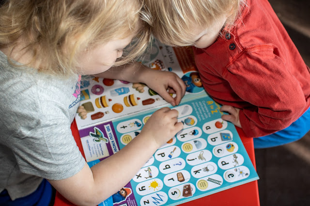 2 children leaning over a magazine and looking at an activity about the alphabet