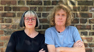 Grayson Perry in a blue T shirt and Philippa Perry in a black top with red glasses both standing in front of a brick wall.