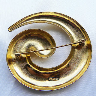 Curled Monet brooch with logo on the reverse