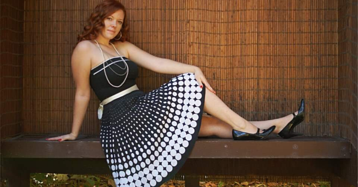 Red haired woman sitting on a bench, leaning back, and wearing a black with white polka dots dress.
