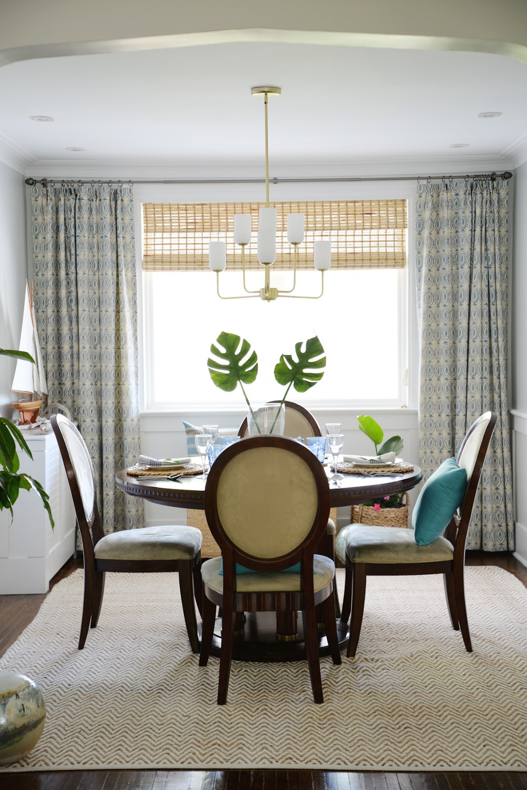 Rambling Renovators | tropical dining room, round dining table, Hinkley Harlow chandelier, tonic living naga blue curtains