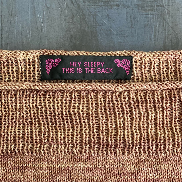 black and pink label in the back of knitted garment that reads Hey Sleepy This is the Back