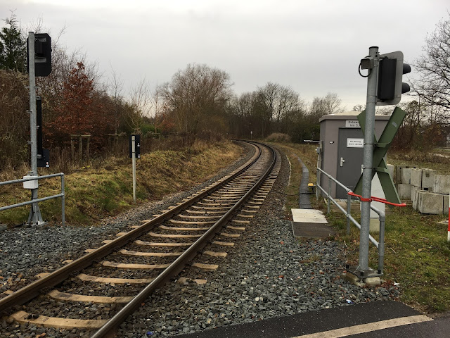 Mittig das geschotterte Gleis, links ein kleines und ein höheres Signal von hinten, rechts der Schiene ein kleines graues Häuschen. Davor ein Andreas-Kreuz mit Blinklicht. Auf dem Rasen liegen Betonblöcke.