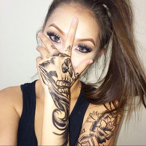 Vemos a una chica que se tapa la boca, en su mano un tatuaje de calavera