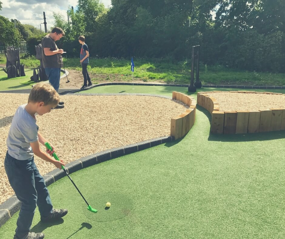 Little boy hits golf ball into a tunnel on Highfields Park Adventure Golf