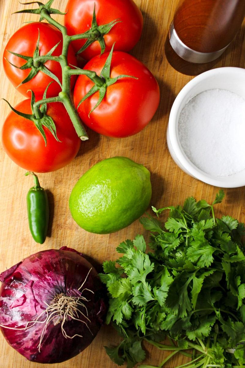 Salsa fresca ingredients on a wood cutting board.