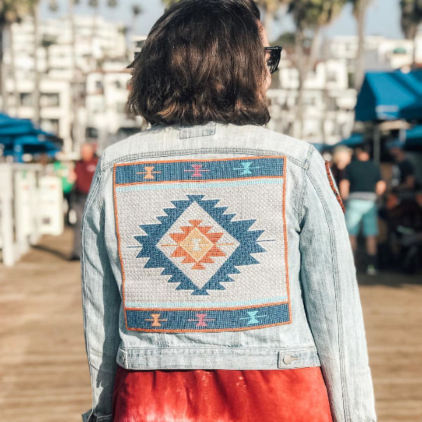 Woman modelling a denim jacket with a southwestern geometric needlepoint design