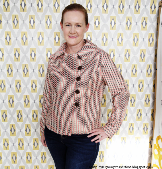 a white lady posing in a jacket against a wallpapered wall