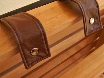 Cintas de couro ecológico ligam as almofadas ao assento e encosto da poltrona através de botões metálicos.