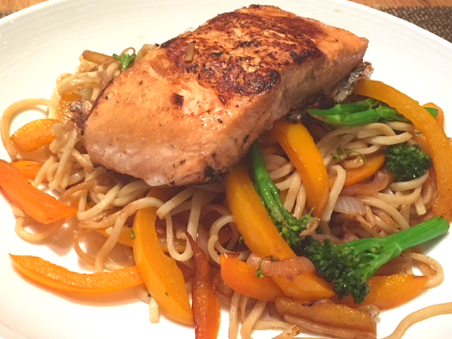 Cooked Asian Salmon on a pile of noodles and vegetables