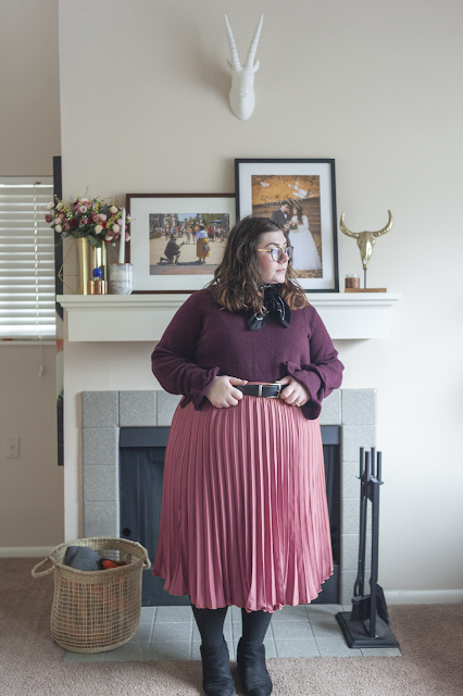 An outfit consisting of a purple sweater tucked into a pink pleated midi length skirt.