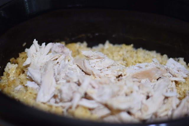 The shredded chicken being returned to the slow cooker.