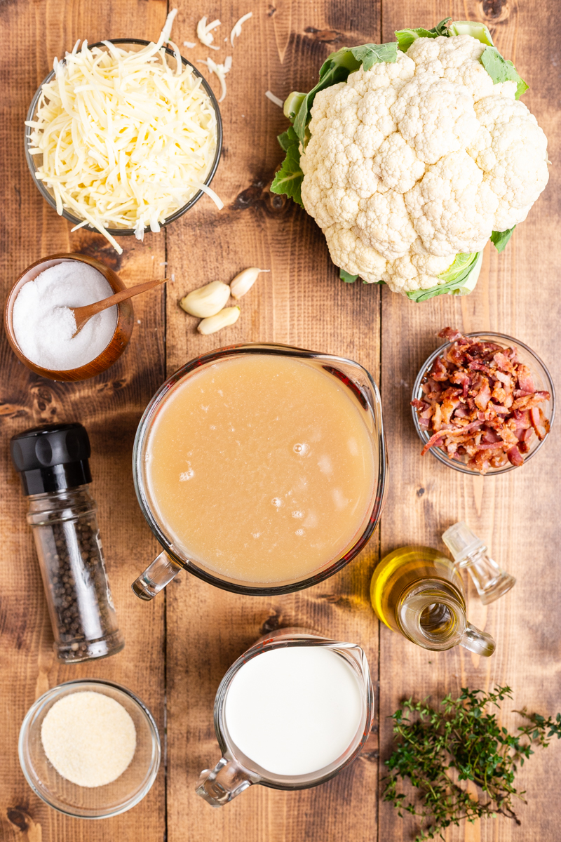 Overhead photo of the ingredients needed to make Easy Cauliflower Cheese Soup on a wooden table.