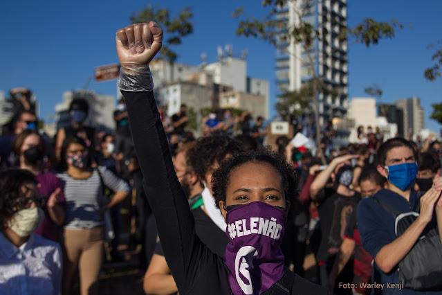 Moça negra, usando máscara com a inscrição #Ele Não, em meio a multidão, ergue o braço com o punho fechado