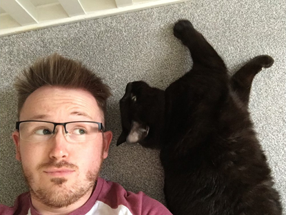 Man lying on the floor next to black cat