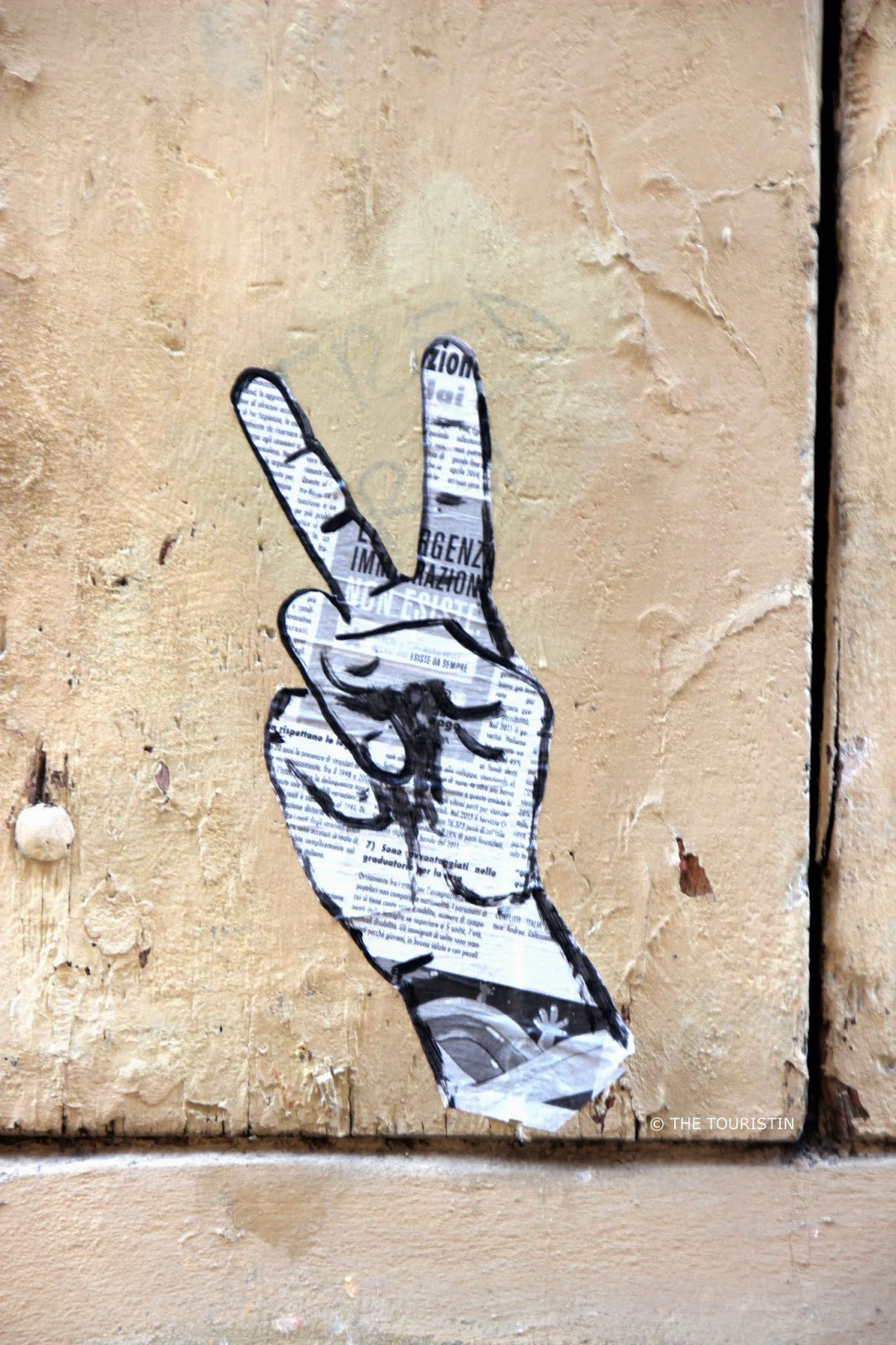A black and white mural of the hand gesture V sign on a beige wall.
