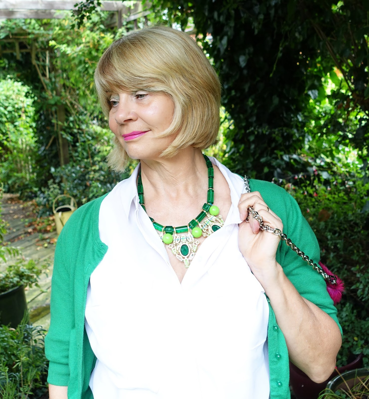 Over 50s woman wearing a green beaded necklace with green patterned skirt and cropped cardigan