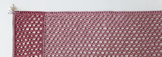 Top view of hand knit pink linen lace table runner with a pearl bead tied to the corner, on a white background.