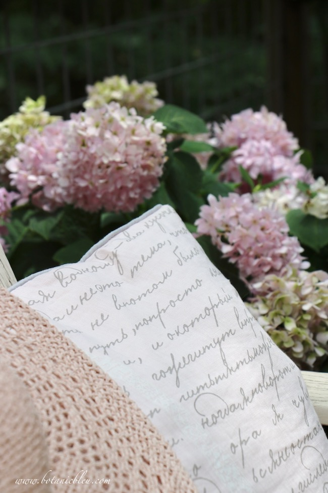Large peach pillow with French script adds comfort to outdoor seating near hydrangeas