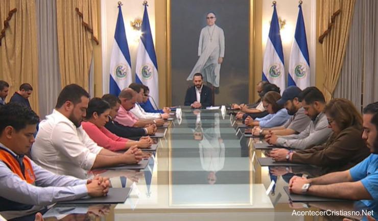 Nayib Bukele orando con su gabinete