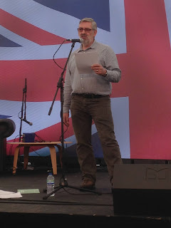 Photo of Seamus reading in front of very large Union Jack projected on screen