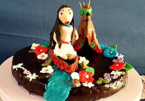Tarta de fondant con la imagen de Pocahontas en una barca yendo por un río.
