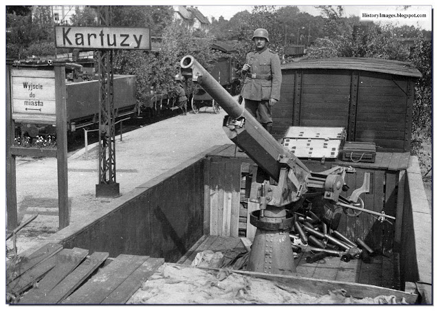 A German soldier stands guard over a captured Polish 75 mm anti-aircraft gun atop a railroad car in 1939