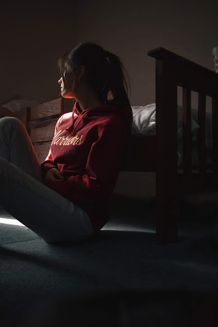 A young girl sitting alone in a seemingly dark room being thoughtful and sad