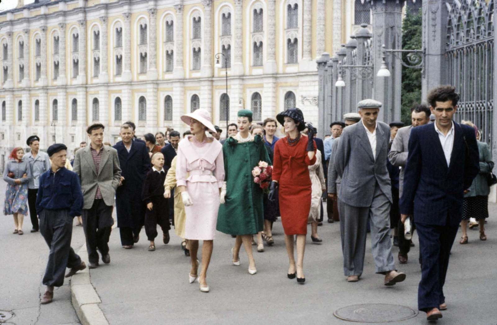 Trailed by a crowd of locals, a trio of Dior fashion models including model Kouka Denis walk along a sidewalk, Moscow, Soviet Union, 1959.