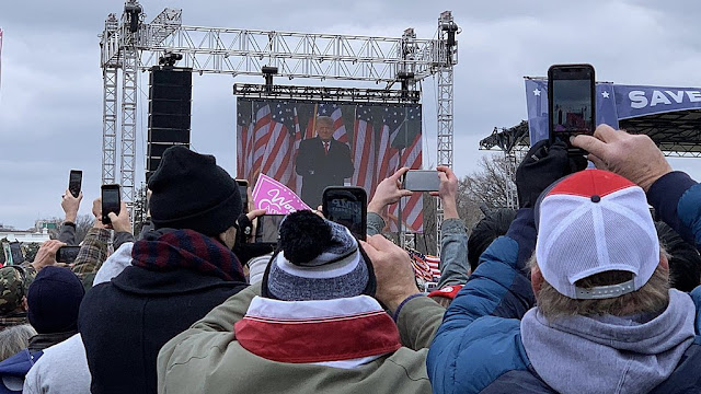 Outdoor crowd watching Trump on giant video screen
