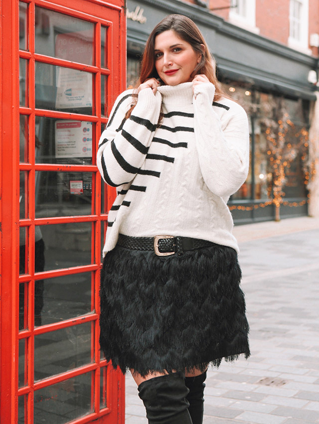 Striped and Cable knit sweater in London with phone box and fringe skirt