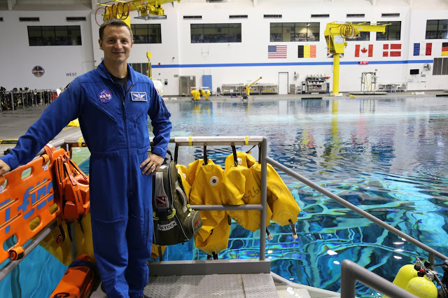a man in an NASA uniform stands by a training pool