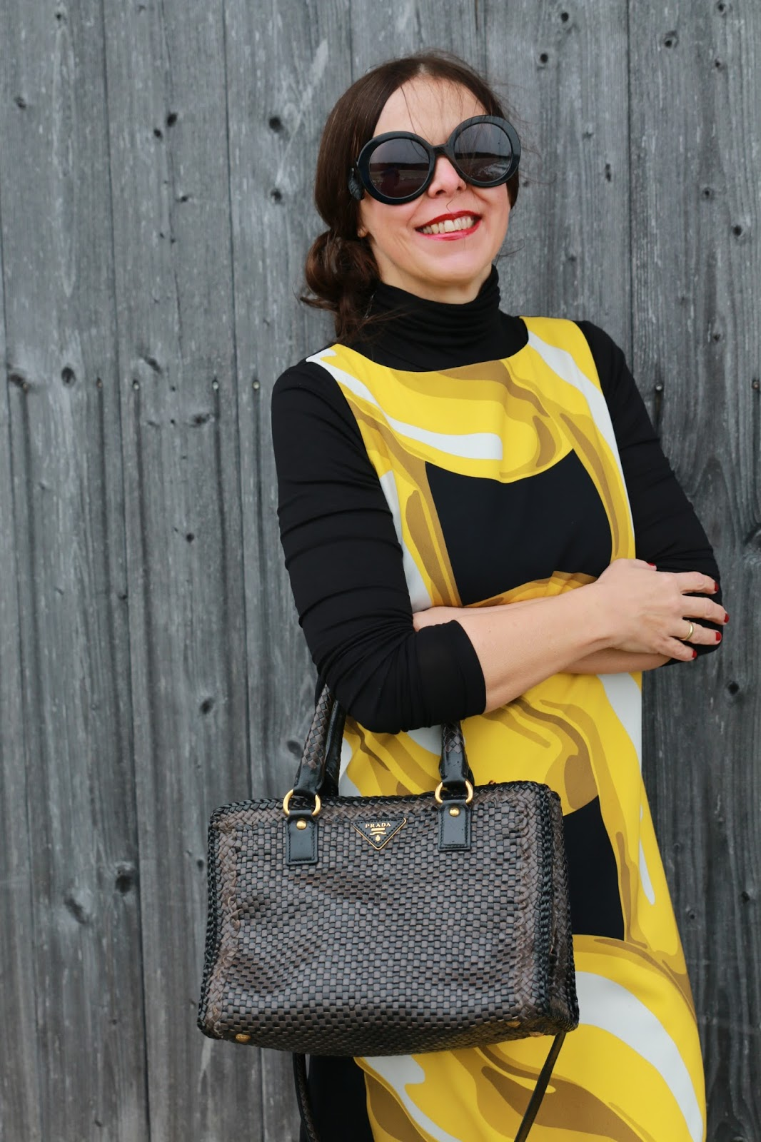 Look prada sun glasses black, Moschino chain dress, black turtleneck sweater, black buckle shoes, grey-black Prada bag