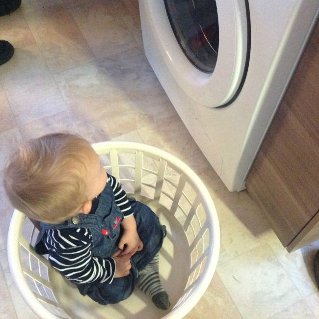 Baby sat in washing basket